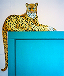 Free standing painting of a perched leopard, painted on wood.